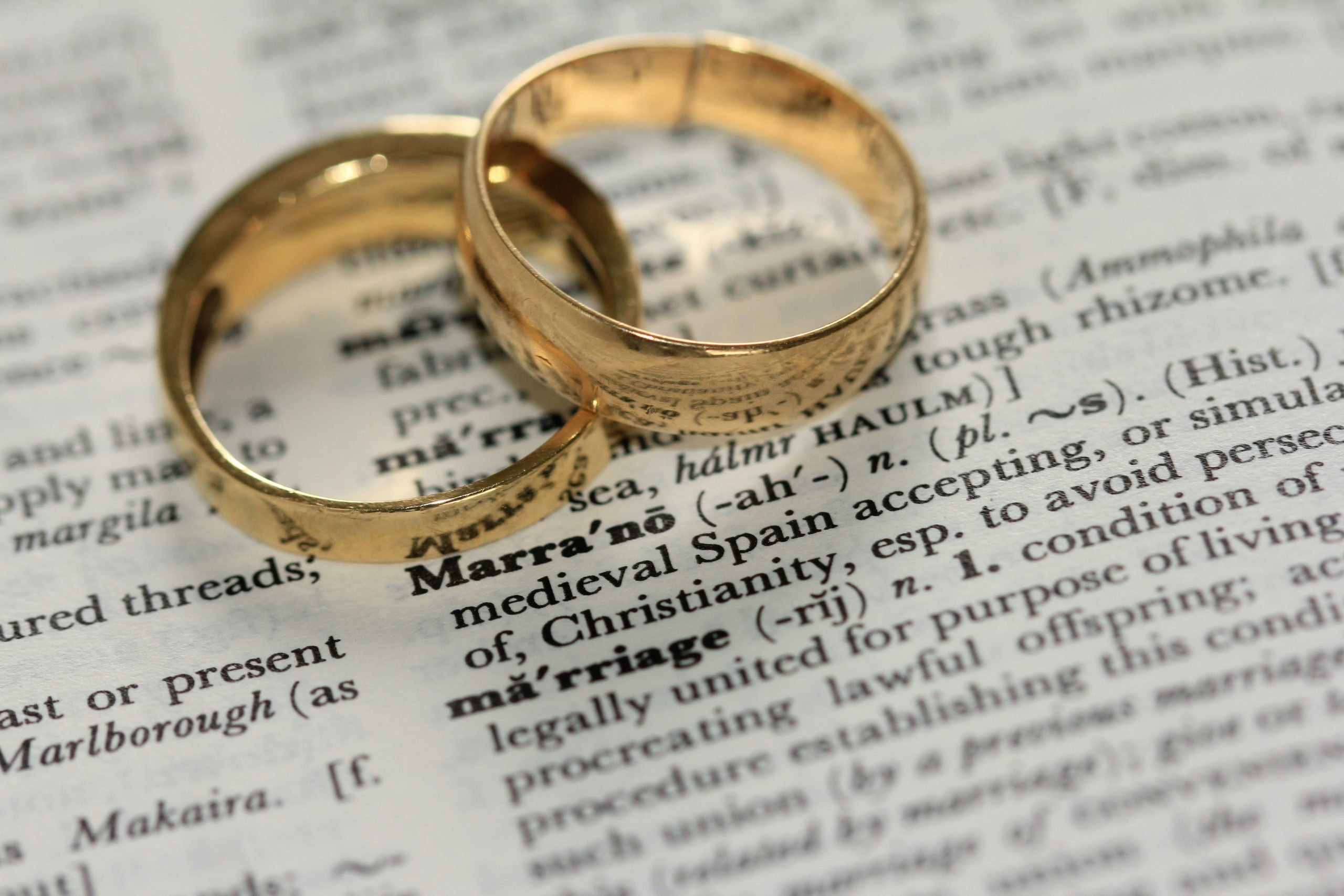 two gold wedding rings together on a page of writing with the definition of marriage