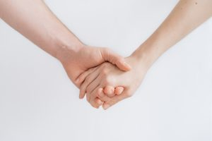 two people holding hands with a white background